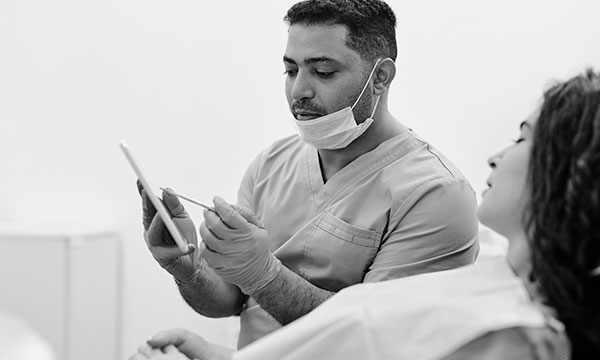 dentist holding tablet and discussing treatment with patient whilst they sit in dental chair