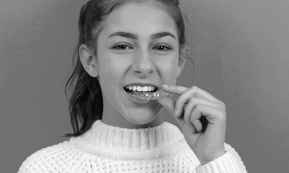 image of young woman with orthodontic aligners in hand